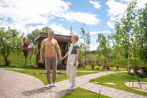 Kochająca dojrzała para trzymająca się za ręce w parku
