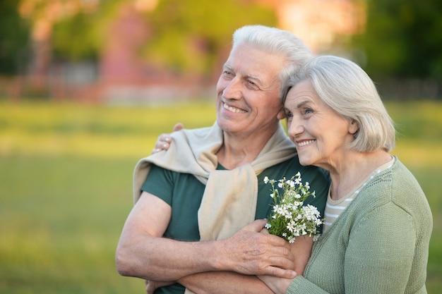 Kochająca dojrzała para w letnim parku z kwiatami