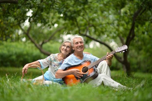 Kochająca dojrzała para z gitarą w letnim parku