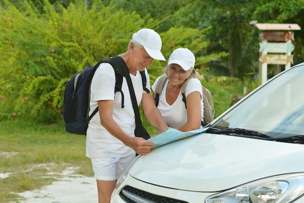 Kochająca dojrzała para z mapą w pobliżu samochodu latem