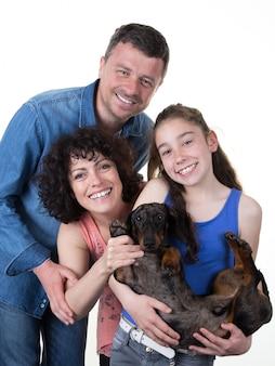 Kochająca i uśmiechnięta rodzina z młodą dziewczyną i jej psem odizolowywającymi na bielu