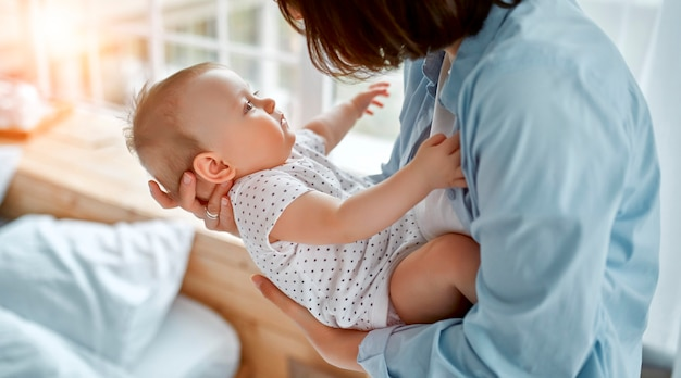Kochająca mama opiekująca się jej nowo narodzonym dzieckiem w domu. mama i chłopiec bawi się w słonecznej sypialni. rodzic i małe dziecko odpoczywa w domu. rodzinna zabawa razem. opieka nad dziećmi, koncepcja macierzyństwa.