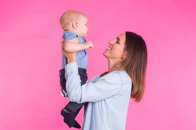 Kochająca matka bawi się z chłopcem na różowym tle