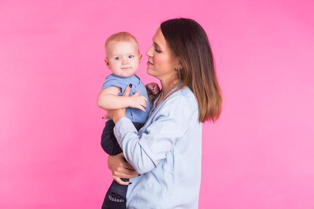 Kochająca matka bawi się ze swoim chłopcem na różowej ścianie.
