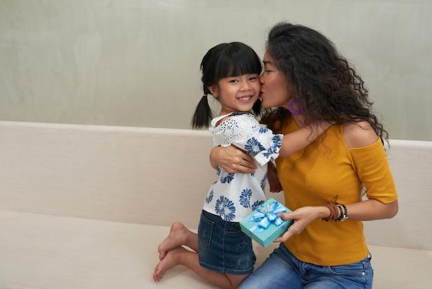 Kochająca matka całuje córkę w domu