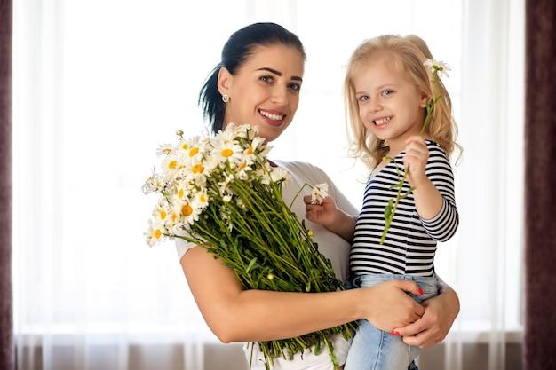 Kochająca matka i córeczka w domu z bukietem stokrotek. rodzina dobrze się razem bawi.