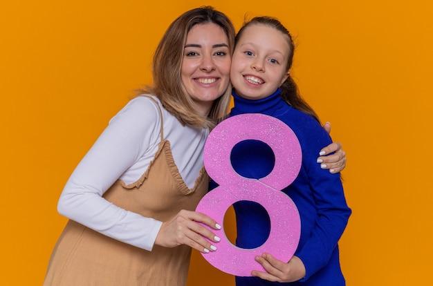 Kochająca matka i córka trzymające numer osiem wykonane z kartonu, patrząc na przód, uśmiechając się radośnie świętując międzynarodowy dzień kobiet stojąc nad pomarańczową ścianą