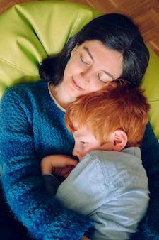 Kochająca matka przytula syna do koszmarów, które usiłują go zasnąć. koncepcja bezsenności i bezsenności. samotna kobieta z dzieckiem w domu. rodzinny styl życia w domu z dziećmi.