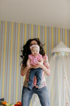Kochająca młoda matka śmiejąc się obejmując uśmiechający się ładny zabawny córka dziecko korzystających czas razem w domu