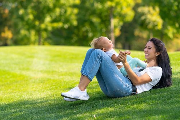 Kochająca młoda matka śmiejąca się ze swoim niemowlęciem, gdy bawią się razem na zielonej trawie w parku lub ogrodzie w cieniu drzewa
