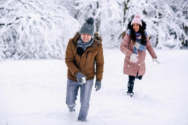 Kochająca młoda para bawić się śnieżkami w winter park