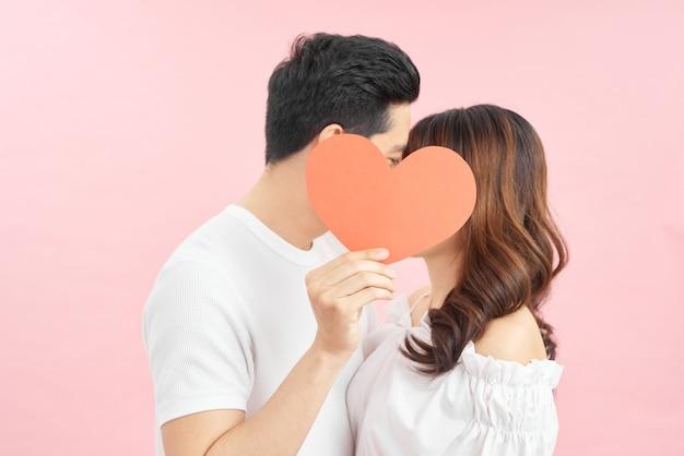 Kochająca młoda para całuje się za czerwonym papierowym sercem na różowym tle