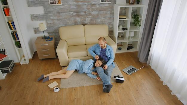 Kochająca młoda para relaks na dywanie w salonie.