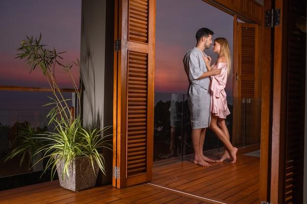 Kochająca młoda para stoi na balkonie i przytula o zachodzie słońca. romantyczny wieczór w hotelu