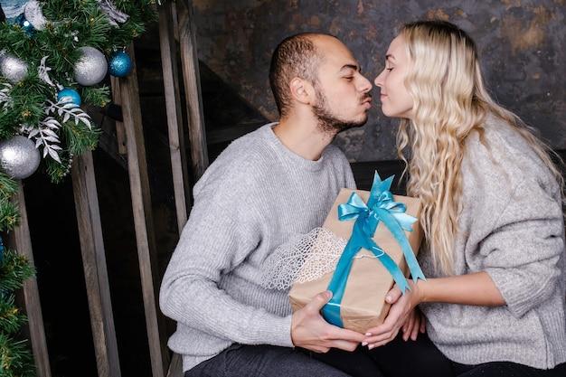 Kochająca młoda para wymienia prezenty na nowy rok. mąż całuje żonę i daje prezent na nowy rok. prezent na boże narodzenie i nowy rok w domu.