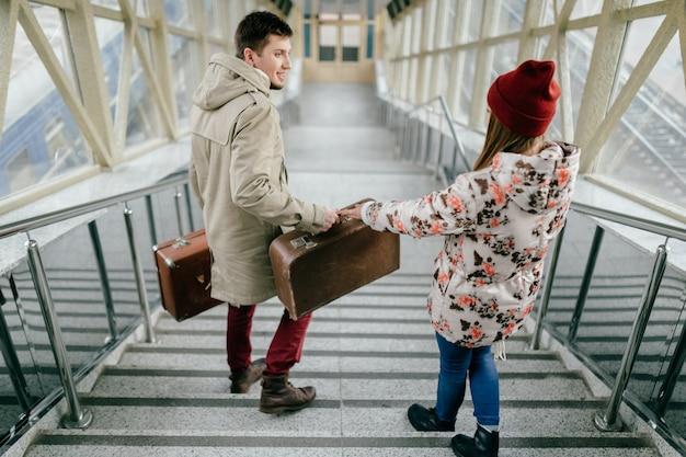 Kochająca młoda para z walizkami chodzenie po schodach.