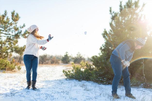Kochająca para bawić się śnieżkami w zimie w lesie. rzuć sobie śnieg. śmiej się i baw się dobrze