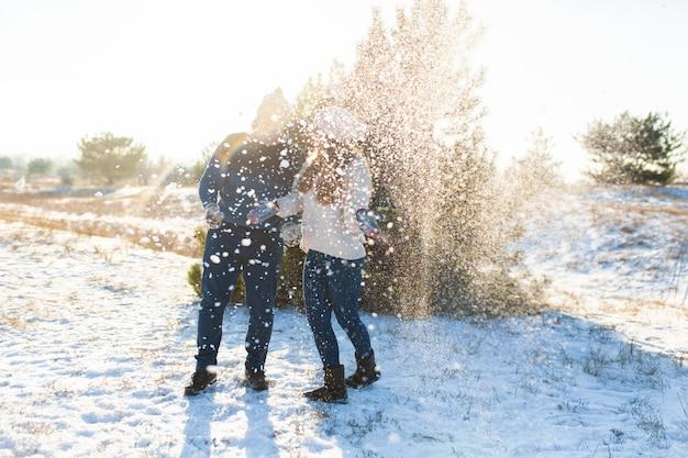 Kochająca para bawić się śnieżkami w zimie w lesie