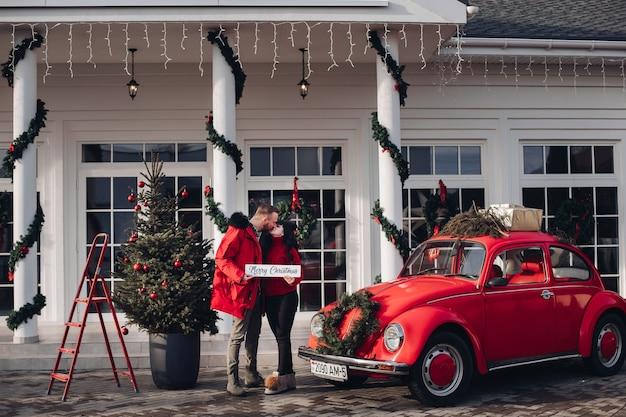 Kochająca para całuje obok czerwonego rocznika samochodu, jodły i domu udekorowanego na boże narodzenie i nowy rok.