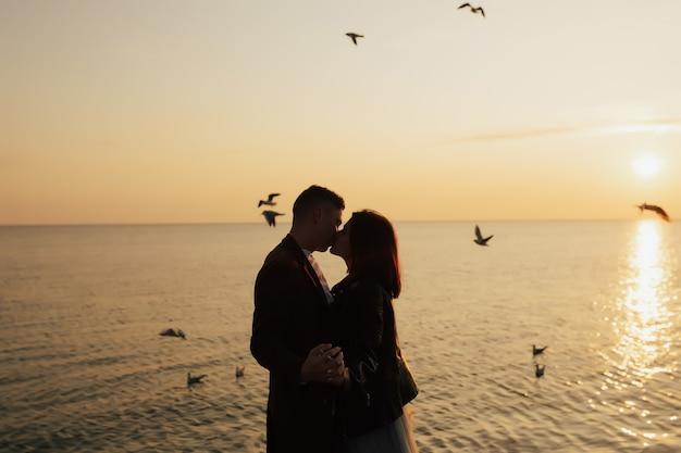 Kochająca para całuje się na morzu o zachodzie słońca