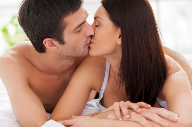 Kochająca para całuje w łóżku. piękna młoda kochająca para leży w łóżku i całuje