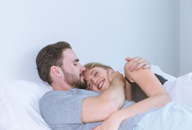 Kochająca para całuje w łóżku. szczęśliwa para leży razem w łóżku.