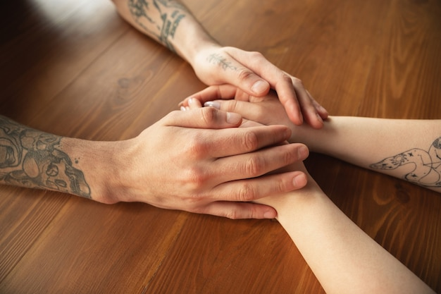 Kochająca para kaukaski trzymając się za ręce zbliżenie na drewnianym stole. romantyczny, miłosny, relacyjny, czuły dotyk. wspierająca i pomocna dłoń, rodzinna, ciepła. razem, uczuciami i emocjami.