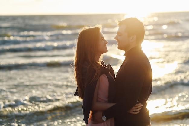 Kochająca para na pierwszej randce spotka zachód słońca nad morzem