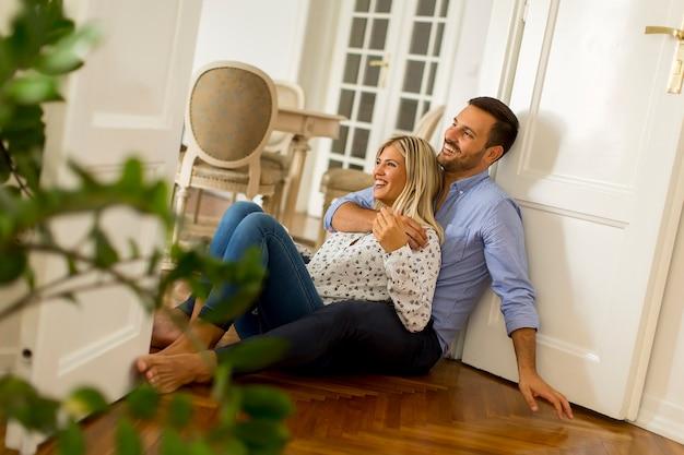 Kochająca para patrzeje each inny podczas gdy pijący czerwone wino na podłoga