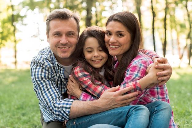 Kochająca para patrzeje kamerę ściska ich córki w parku