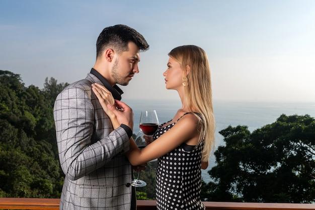 Kochająca para pije czerwone wino na balkonie. romantyczna atmosfera miłości i związków
