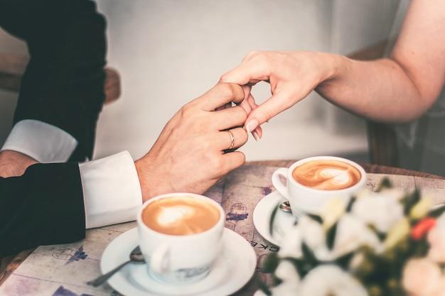 Kochająca para pije kawę po ślubie. ręce nowożeńców