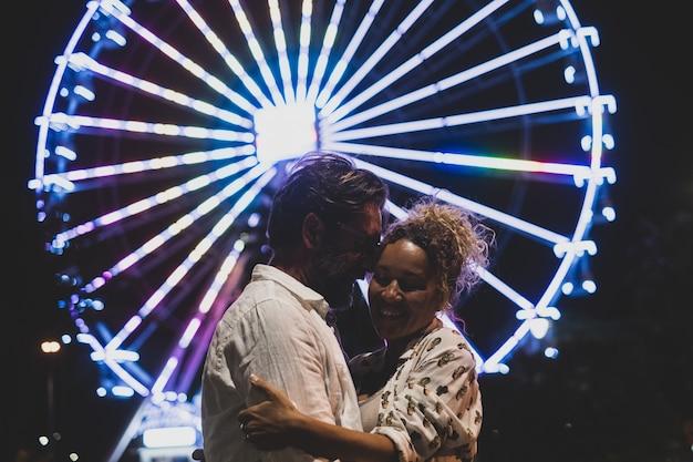 Kochająca para przytula się namiętnie na ulicy przed oświetlonym diabelskim młynem w nocy. para romansuje i spędza czas na świeżym powietrzu podczas wakacji w nocy