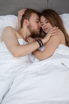 Kochająca para przytulanie leżąc w łóżku