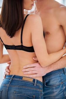 Kochająca para przytulanie. przycięty obraz pięknej młodej pary przytulającej się bez koszuli