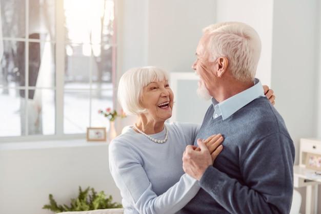 Kochająca para. radosny starszy mąż i żona tańczą w salonie, uśmiechając się do siebie szeroko