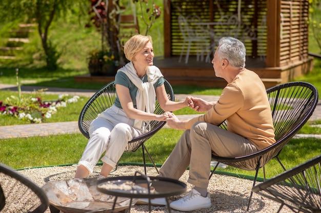 Kochająca para siedzi w fotelach w ogrodzie