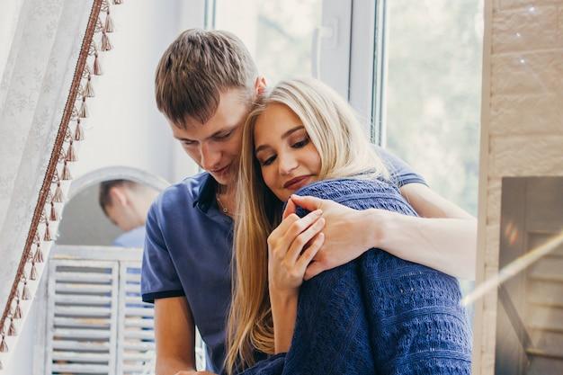 Kochająca para siedzi w oknie, kochające i delikatne spojrzenie. pozytywne emocje, uśmiechnięte twarze. para przytulanie i patrząc na siebie. mężczyzna i kobieta się kochają