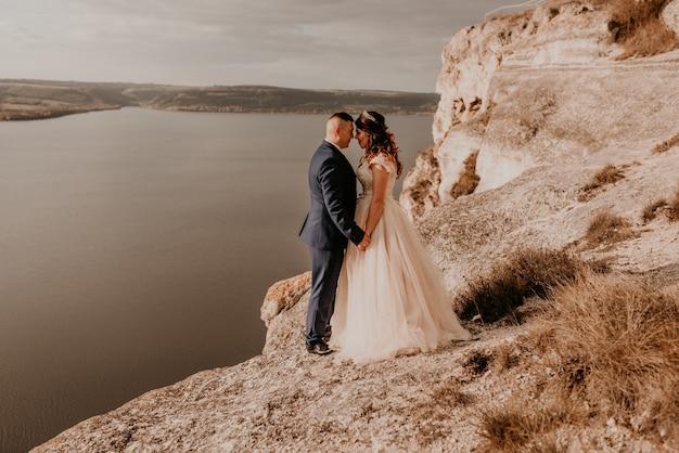 Kochająca para ślubna nowożeńców w białej sukni i garniturze spaceruje latem po górze nad rzeką