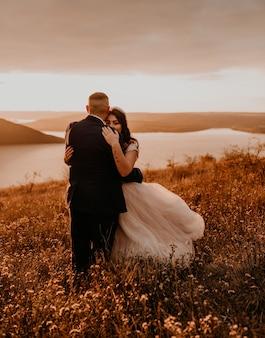 Kochająca para ślubna nowożeńcy w białej sukni i garniturze spacer uścisk całujący wir na wysokiej trawie w letnim polu na górze nad rzeką