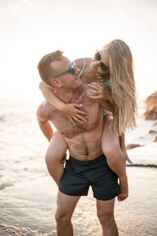 Kochająca para spaceruje po plaży nad morzem. młoda rodzina o zachodzie słońca nad morzem śródziemnym. koncepcja wakacji. kobieta w stroju kąpielowym i mężczyzna w krótkich spodenkach o zachodzie słońca nad morzem. selektywne skupienie.