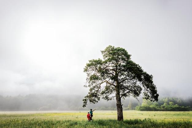Kochająca para spotyka świt w terenie. mglisty poranek. facet i dziewczyna w pobliżu drzewa. para podróżuje. mężczyzna i kobieta w polu. samotne drzewo facet podniósł dziewczynę. miłośnicy podróży. chodź za mną