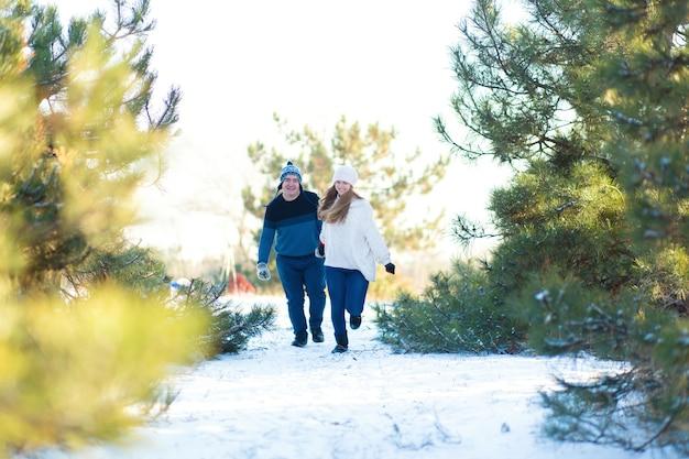 Kochająca para trzymając się za ręce biegnie przez zimowy las. śmiej się i baw się dobrze.
