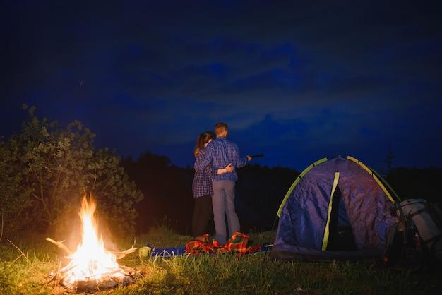 Kochająca para turystów, ciesząc się sobą, stojąc przy ognisku w nocy pod wieczornym niebem w pobliżu drzew i namiotu