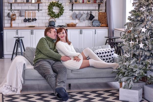 Kochająca para w ciepłych swetrach obejmuje i całuje. zakochani świętują nowy rok w domu, siadają w białej kuchni przy choince, trzymają się za ręce, patrzą na siebie. zamknij się portraite, kopia przestrzeń