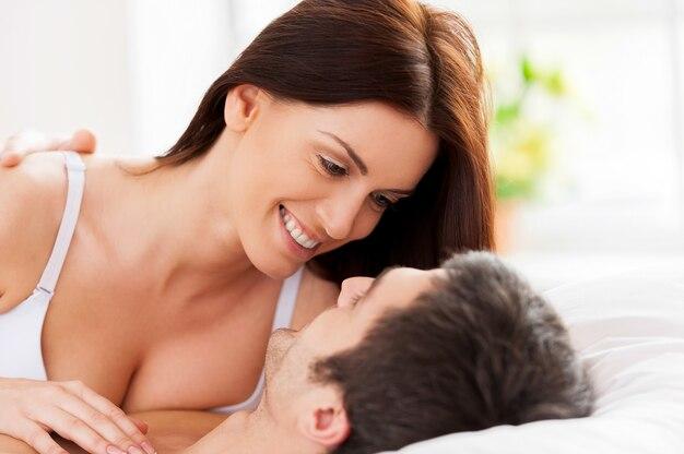 Kochająca para w łóżku. piękna młoda kochająca para leżąca w łóżku i patrząca na siebie