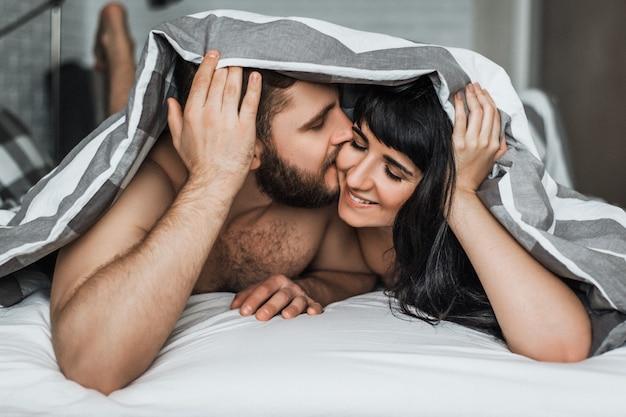 Kochająca para w łóżku uprawia seks. facet i dziewczyna całuje w łóżku. noc poślubna. kochać się. kochankowie w łóżku. relacja mężczyzny i kobiety. seks między mężczyzną a kobietą. uściski w łóżku.