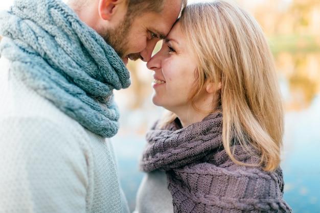 Kochająca para w trykotowym odzieżowym romantycznym portrecie z odbijającym jeziorem na tle