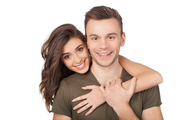 Kochająca para. wesoła młoda kobieta przytulająca swojego chłopaka i patrząca w kamerę stojąc na białym tle