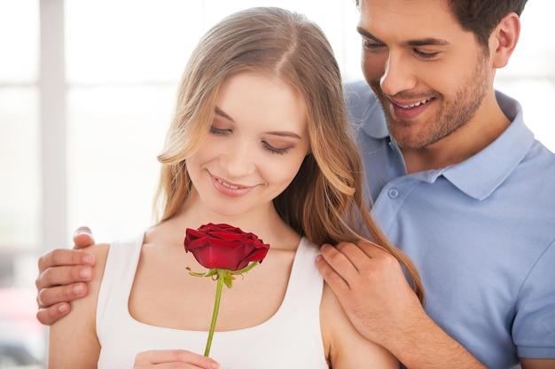 Kochająca para. wesoła młoda kochająca para stoi blisko siebie, podczas gdy kobieta trzyma w dłoni czerwoną różę
